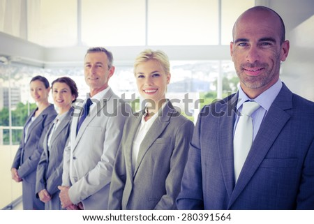 Business team smiling at the camera in the office