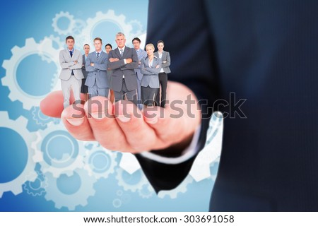 Business team standing arms crossed against white wheels and cogs on blue