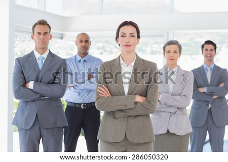 Business team standing arms crossed in the office