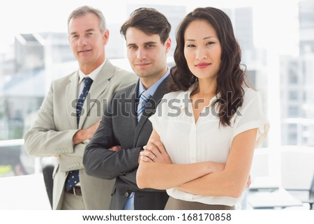 Business team standing in a row smiling at camera in the office