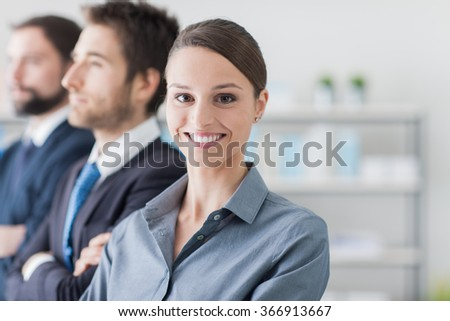 Business team standing in line during a meeting, a woman is smiling at camera