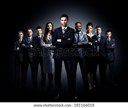 business team standing over a dark background - stock photo