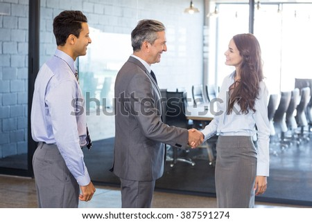 Business team standing together and interacting in office - stock photo