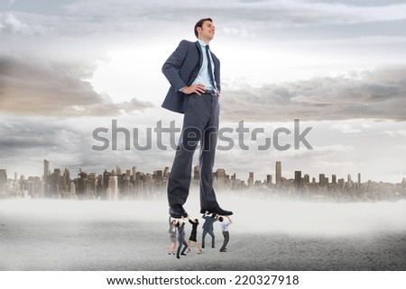 Business team supporting boss against large city on the horizon
