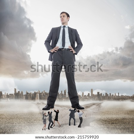 Business team supporting boss against path in yellow field leading to city - stock photo