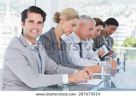 Business team taking notes during conference in the office - stock photo