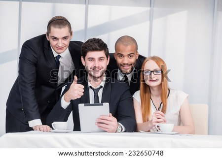 Business team together. Young businessmen holding a tablet in her hand while his colleagues showing a thumbs up. Businesspeople sitting at a table at a meeting in the office. - stock photo