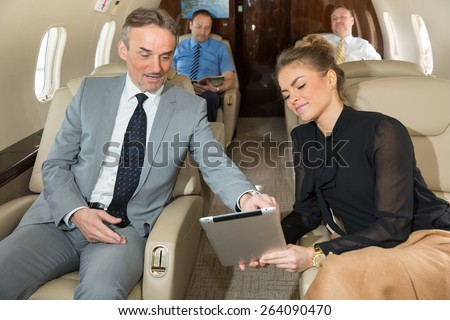 business team traveling in corporate jet and discussing a presentation - stock photo