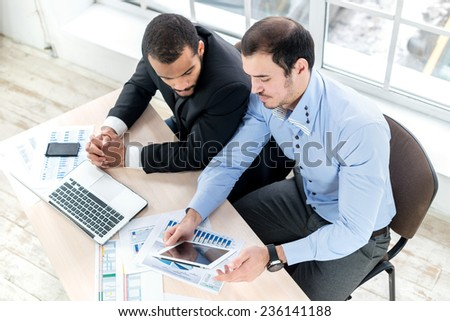 Business team. Two serious businessman working on a tablet and a laptop at his desk in the office in the formal wear. - stock photo