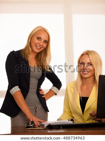Business team - two women work in the office checking database