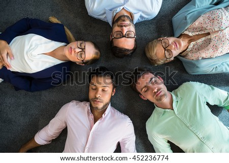 Business team with eyes closed lying on the floor with head together in the office - stock photo