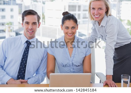 Business team with laptop smiling at camera at desk in office
