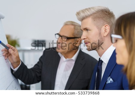 Business team with senior manager standing in front of a flip chart