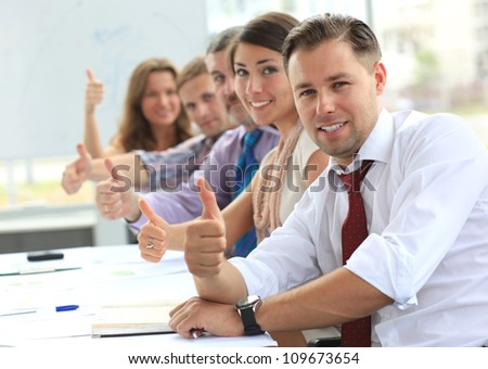 Business-team with thumbs up after a presentation in office - stock photo