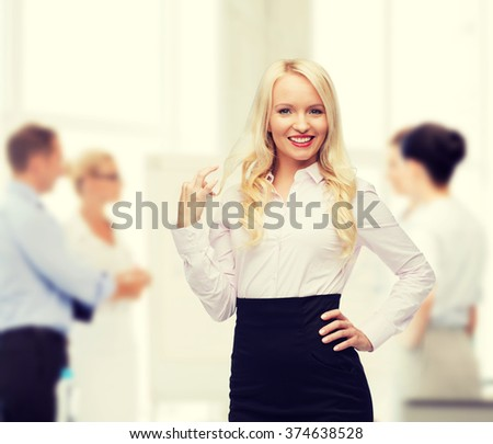 business, team work and people concept - smiling businesswoman, student or secretary over group of colleagues in office background - stock photo