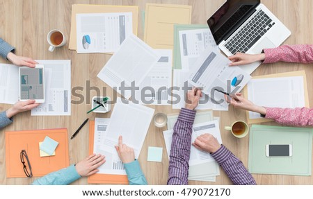 Business team working at office desk with paperwork, a laptop and a digital tablet, teamwork and finance concept