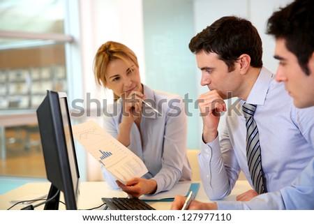 Business team working in front of desktop - stock photo