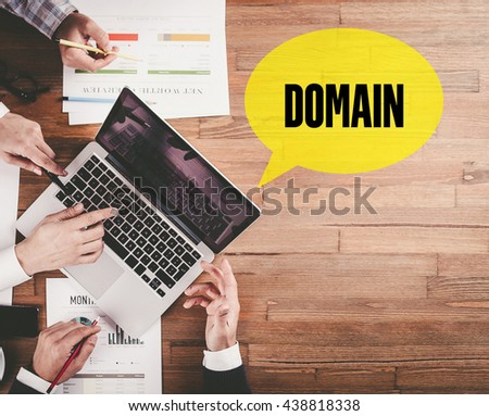 BUSINESS TEAM WORKING IN OFFICE WITH DOMAIN SPEECH BUBBLE ON DESK - stock photo