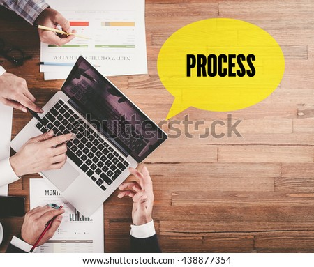 BUSINESS TEAM WORKING IN OFFICE WITH PROCESS SPEECH BUBBLE ON DESK - stock photo