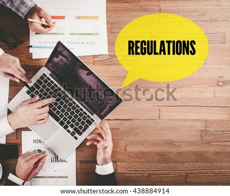 BUSINESS TEAM WORKING IN OFFICE WITH REGULATIONS SPEECH BUBBLE ON DESK - stock photo