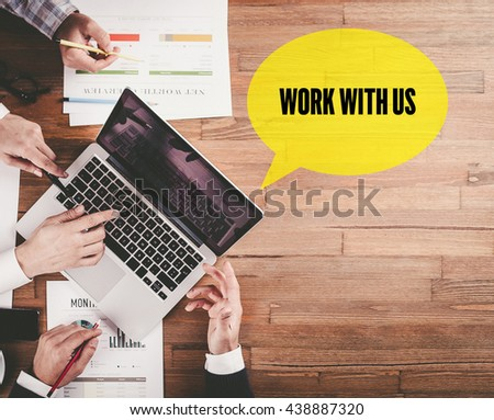 BUSINESS TEAM WORKING IN OFFICE WITH WORK WITH US SPEECH BUBBLE ON DESK - stock photo