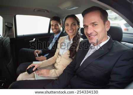 Business team working in the back seat in the car - stock photo