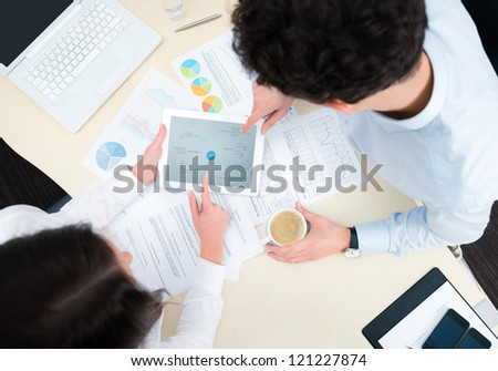 Business team working on a new business plan with modern digital computer. Top view shot. - stock photo