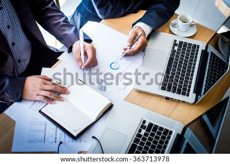 Business team working on a new business plan with modern digital computer. Top view shot