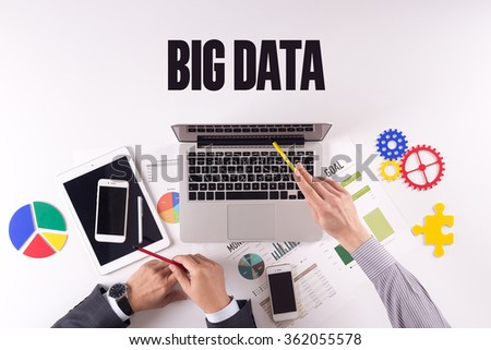 Business team working on desk with a single word BIG DATA - stock photo