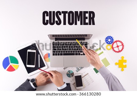 Business team working on desk with a single word CUSTOMER - stock photo