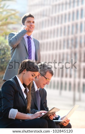 Business team working on digital devices outdoors. - stock photo