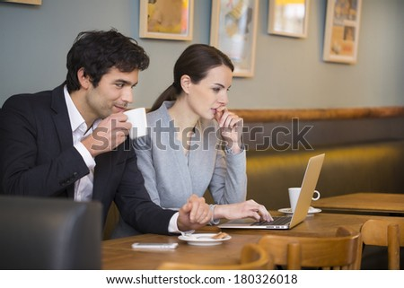 Business team working on laptop at coffee bar - stock photo