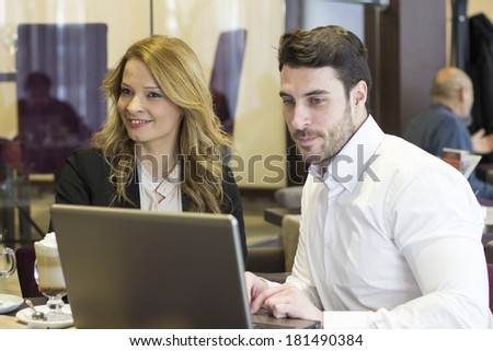 Business team working on laptop at coffee bar in hotel - stock photo