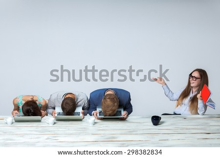 Business team working on their business project together at office on light gray background. all buried his head in the computer screen. boss laughing. copyspace image.  - stock photo