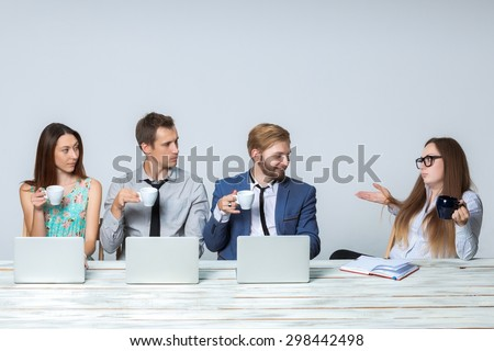Business team working on their business project together at office on light gray background.  all drinking coffee and looking at the boss. copyspace image.  - stock photo