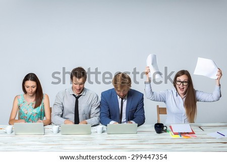 Business team working together at office on light gray background. all working on laptops. boss enjoying a good idea. copyspace image - stock photo