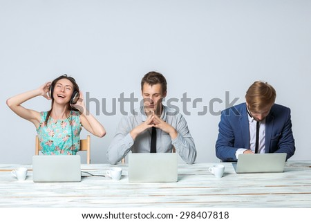 Business team working together at office on light gray background. all working on laptops. girl in headphones enjoying the music - stock photo
