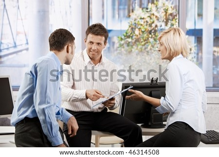 Business team working together in office, people planning, smiling.