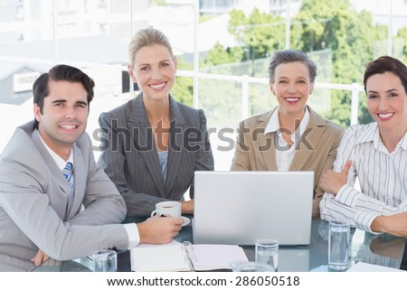 Business team working together on laptop in the office - stock photo