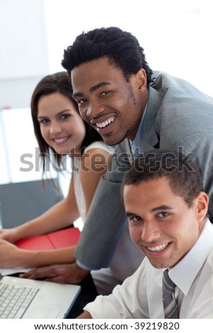 Business team working together with a laptop in office - stock photo