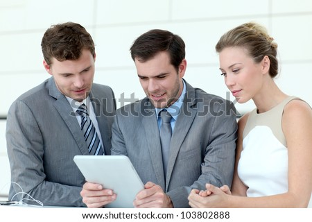 Business team working with electronic tablet - stock photo