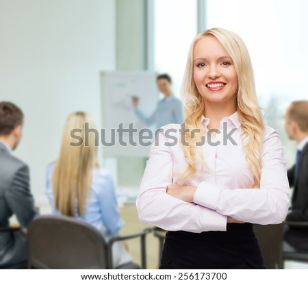 business, teamwork and people concept - smiling businesswoman, student or secretary over office and group of colleagues background - stock photo