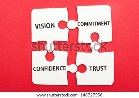 Business teamwork concept of vision, commitment, confidence, trust written on group of jigsaw puzzle pieces - stock photo