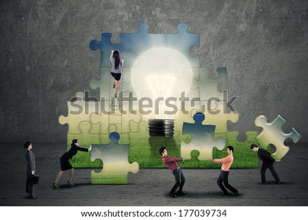 Business teamwork creating a puzzle together - stock photo