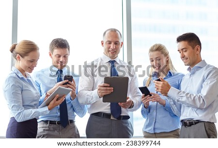 business, teamwork, people and technology concept - business team with tablet pc computers and smartphones meeting in office - stock photo