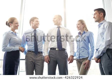 business, teamwork, people and technology concept - smiling business team meeting and talking in office - stock photo
