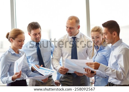 business, teamwork, people and technology concept - smiling business team with papers meeting and talking in office