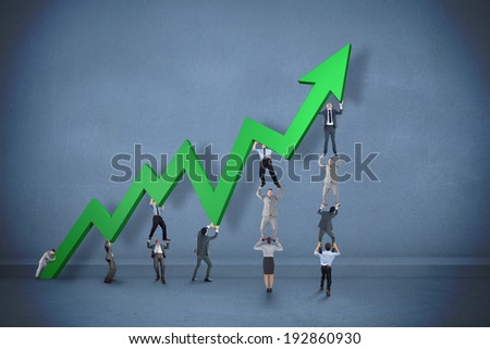 Business teamwork pushing arrow against dark room - stock photo