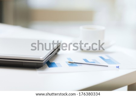business, technology and beverage concept - close up of laptop computer, charts, pen and coffee in office - stock photo