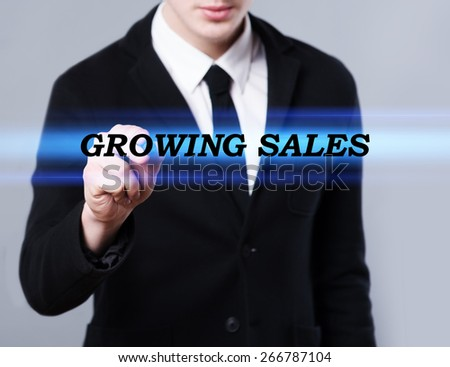 business, technology and internet concept - businessman is writing growing sales text - stock photo